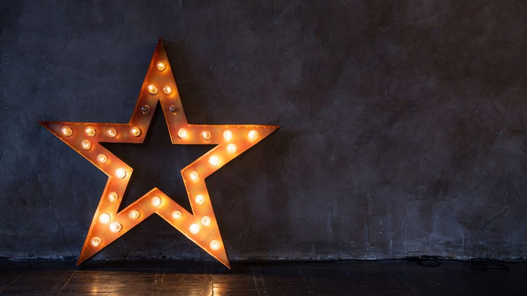 lit up star leaning against a wall
